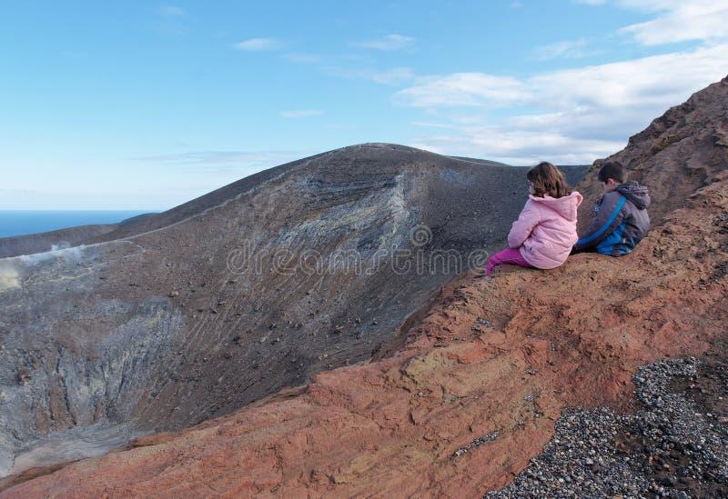 Menina e menino que sentam-se na borda da cratera do vulcão fotos de stock