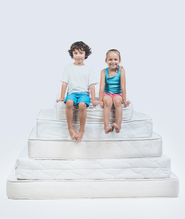Menina e menino que sentam-se sobre a pirâmide do colchão imagens de stock