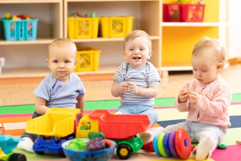 Menina e meninos de bebês do berçário que jogam junto em uma sala do jogo fotos de stock