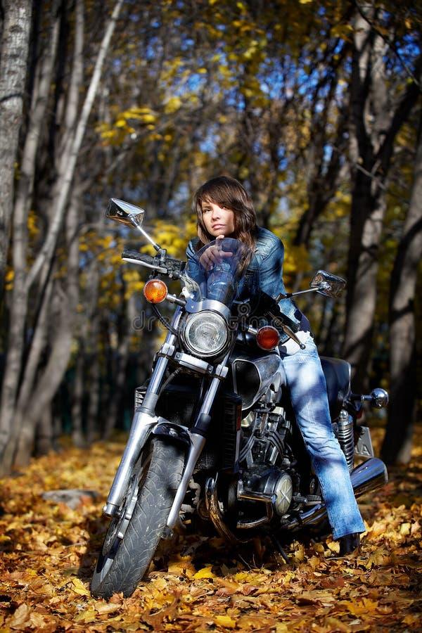 A menina e a motocicleta triguenhas da potência imagens de stock