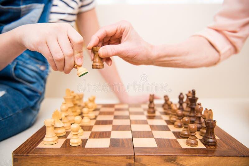 Menina e mulher superior que jogam a xadrez imagem de stock royalty free