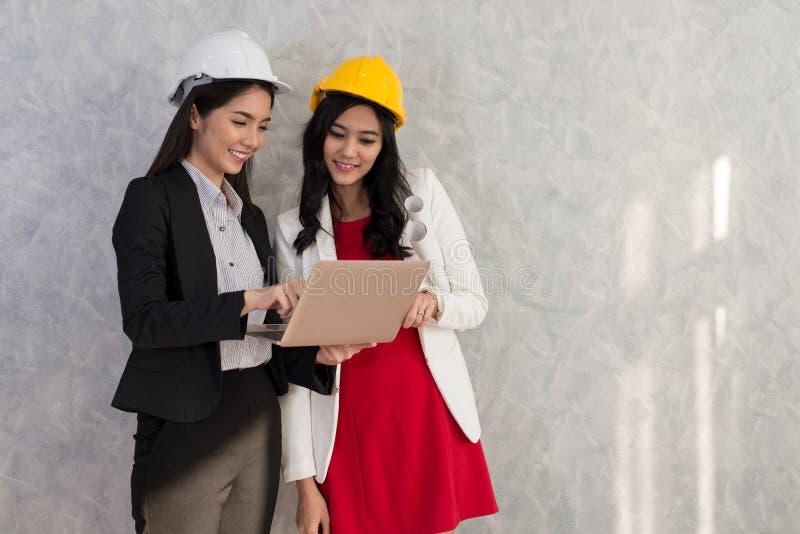 A menina e o coordenador do negócio com povos asiáticos trabalham com portátil AR fotografia de stock royalty free