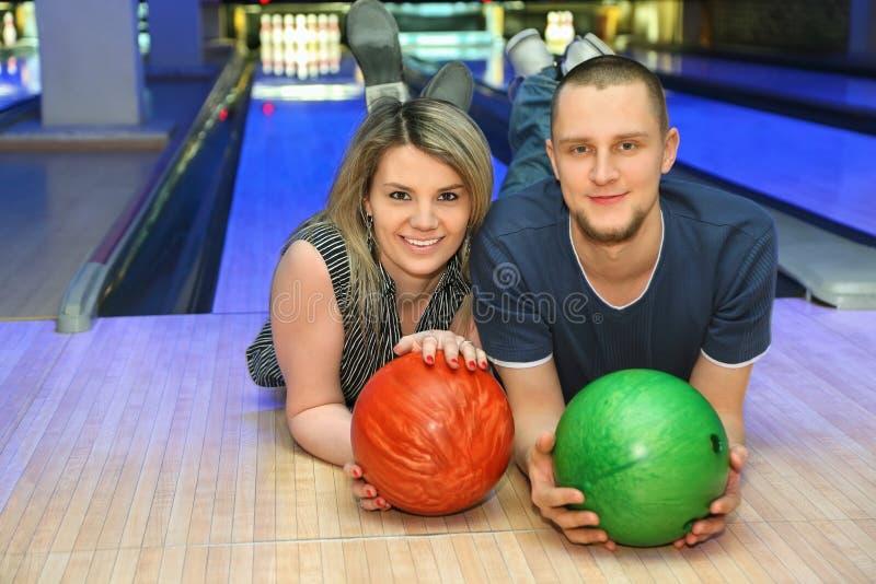 A menina e o homem encontram-se no parquet no clube do bowling foto de stock royalty free