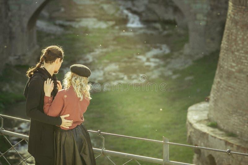 A menina e o homem na ponte, comem com os olhos o homem, relacionamentos bonitos, pares no amor, pares apaixonado nas montanhas G imagens de stock royalty free