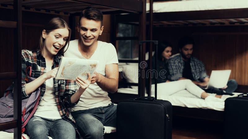 A menina e o homem sentam-se na cama e no olhar no mapa junto imagens de stock royalty free