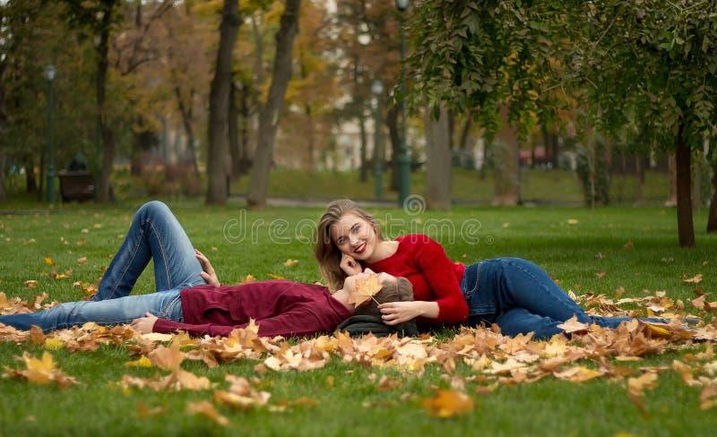 A menina e o indivíduo em camisetas e em calças de brim vermelhas sentam-se no parque na grama verde nas folhas de bordo amarelas imagens de stock royalty free