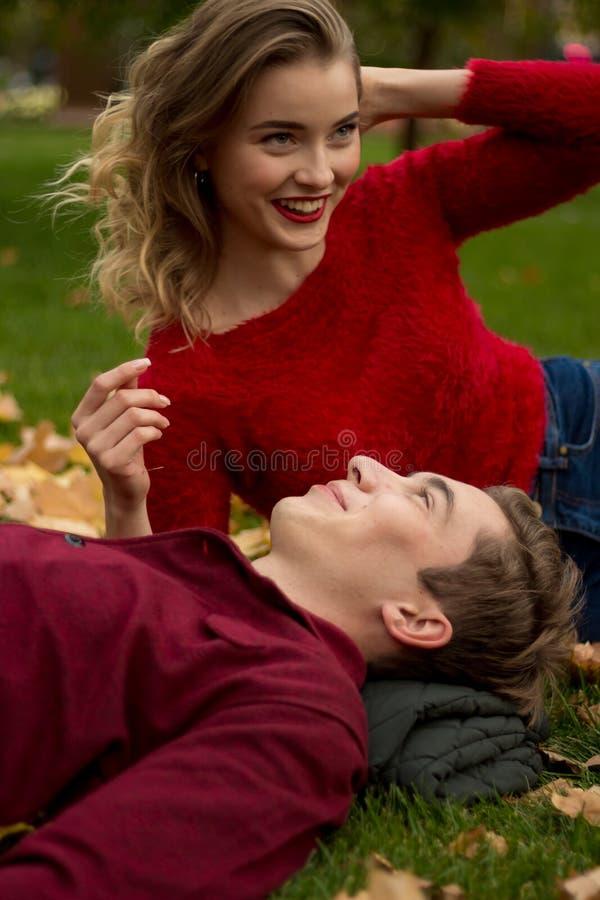 A menina e o indivíduo em camisetas e em calças de brim vermelhas sentam-se no parque na grama verde nas folhas de bordo amarelas imagem de stock