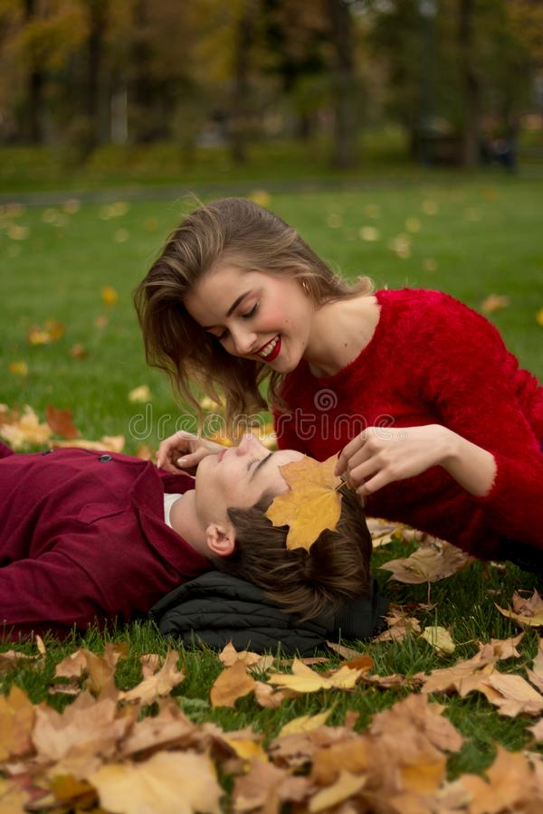 A menina e o indivíduo em camisetas e em calças de brim vermelhas sentam-se no parque na grama verde nas folhas de bordo amarelas fotos de stock