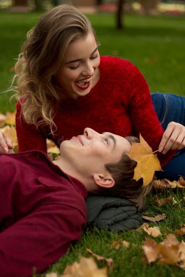 A menina e o indivíduo em camisetas e em calças de brim vermelhas sentam-se no parque na grama verde nas folhas de bordo amarelas imagens de stock
