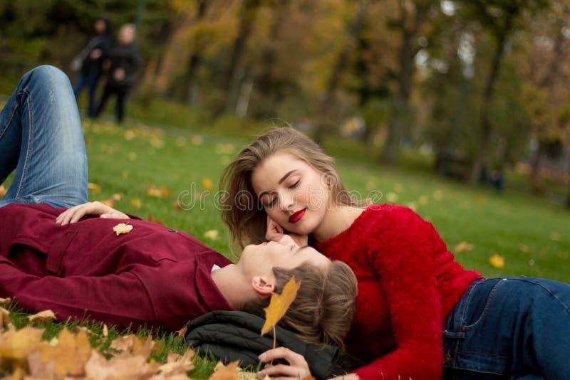 A menina e o indivíduo em camisetas e em calças de brim vermelhas sentam-se no parque na grama verde nas folhas de bordo amarelas foto de stock