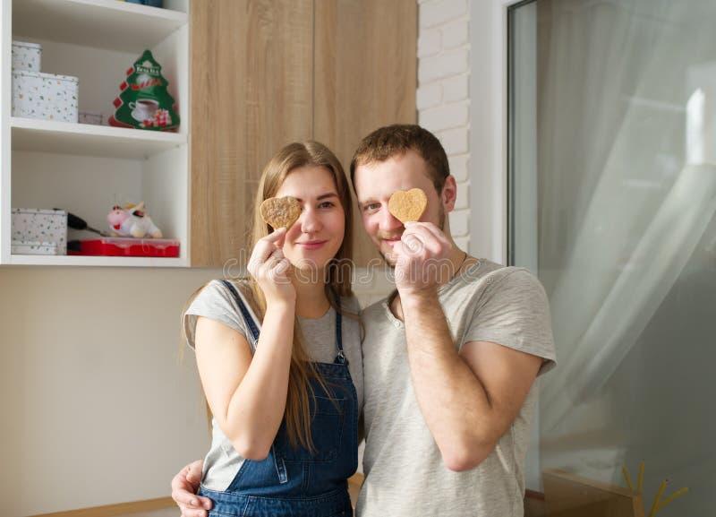 A menina e o indivíduo esconderam os olhos atrás das cookies do gengibre foto de stock royalty free