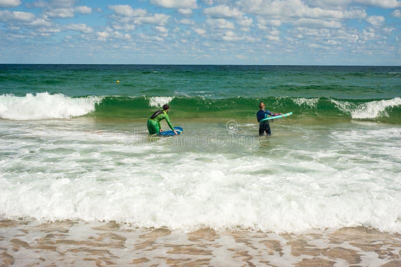 A menina e o menino aprendem montar uma prancha no mar no verão Montada em uma prancha nas ondas em um lugar bonito imagens de stock royalty free