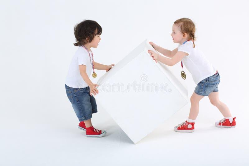 A menina e o menino com medalhas invertem o grande cubo branco fotos de stock royalty free