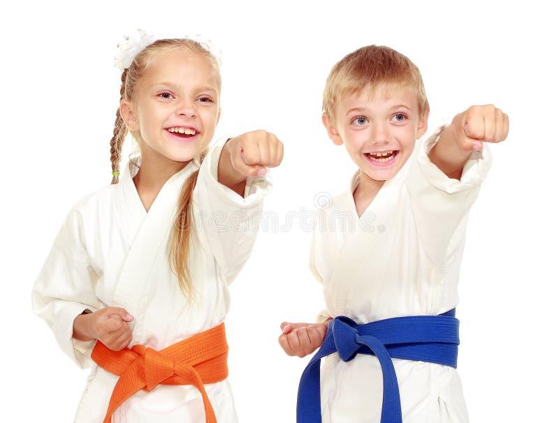 A menina e o menino em um quimono em um fundo branco bateram a mão fotografia de stock royalty free