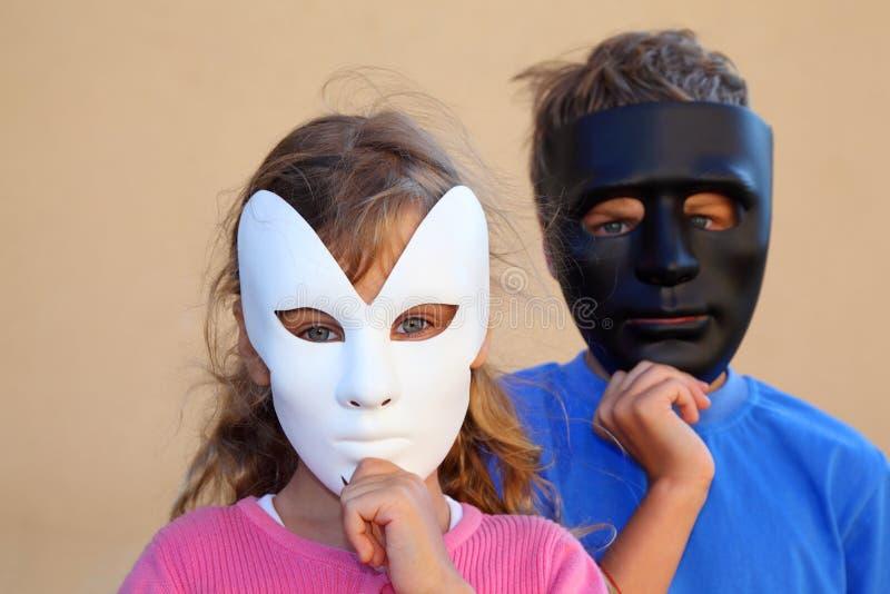A menina e o menino escondem as faces atrás das máscaras fotografia de stock royalty free