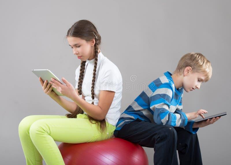 A menina e o menino que olham a almofada marcam telas do PC fotos de stock