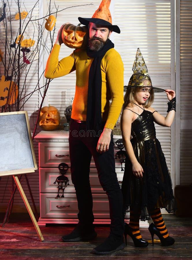 A menina e o pai pequenos têm o divertimento da família no Dia das Bruxas A família feliz comemora o Dia das Bruxas O pai e a men foto de stock