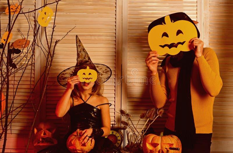 A menina e o pai pequenos vestem máscaras do Dia das Bruxas Caras pequenas da tampa da menina e do pai com cabeças da abóbora Est fotos de stock