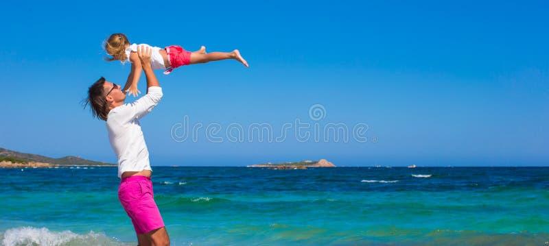 A menina e o paizinho têm o divertimento durante a praia tropical fotografia de stock royalty free
