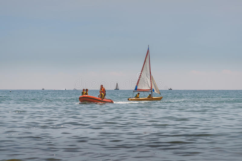 A menina e os meninos montam em um barco inflável de borracha no mar Os meninos aprendem conduzir um bote com uma vela Navigação  imagens de stock