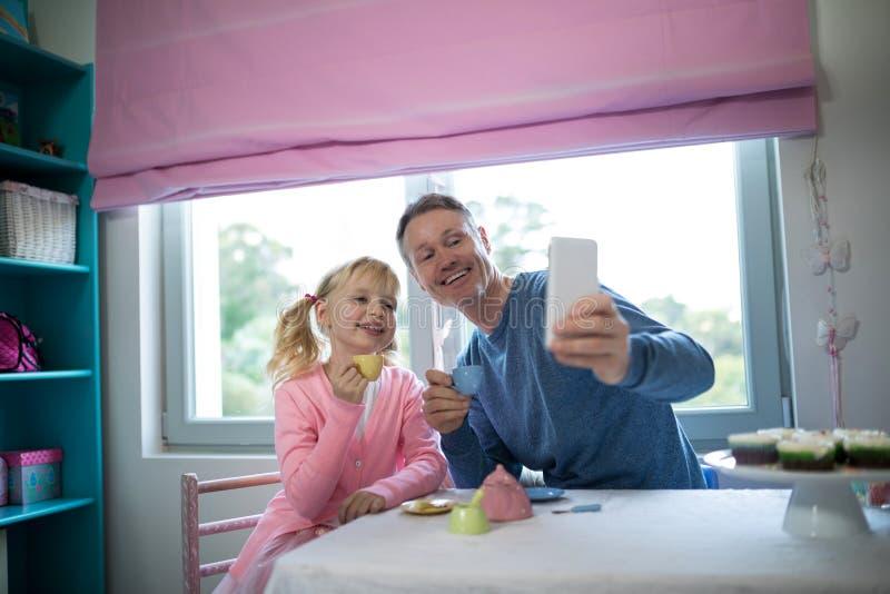 Menina e pai que tomam um selfie ao jogar com um grupo da cozinha do brinquedo foto de stock