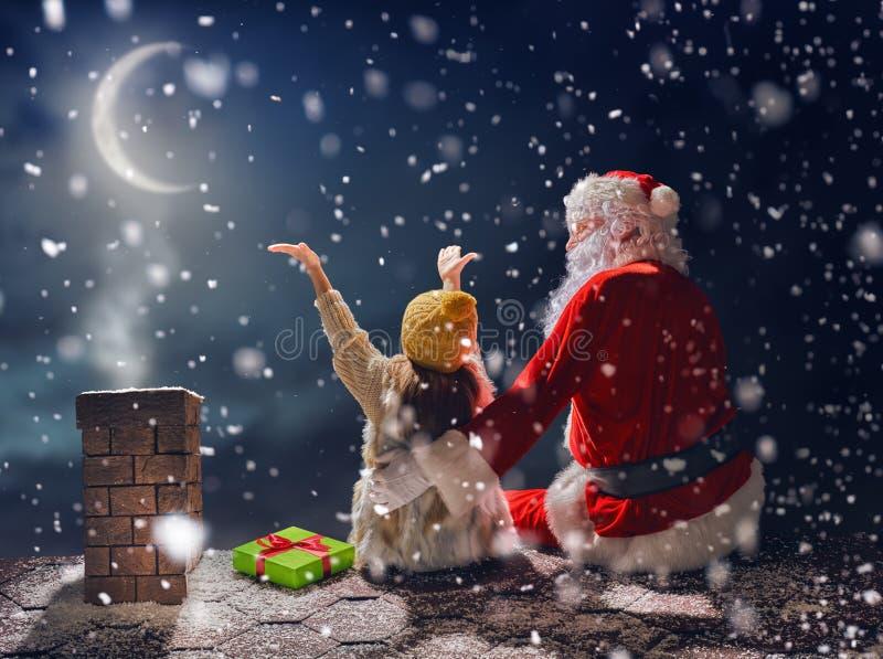 Menina e Santa Claus que sentam-se no telhado imagens de stock