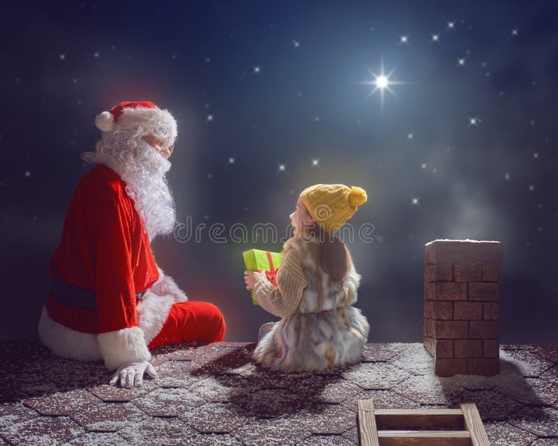Menina e Santa Claus que sentam-se no telhado imagens de stock royalty free