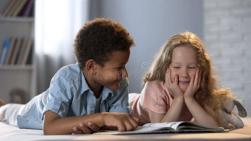 Menina e seu amigo afro-americano que têm o divertimento ao aprender ler o livro imagens de stock