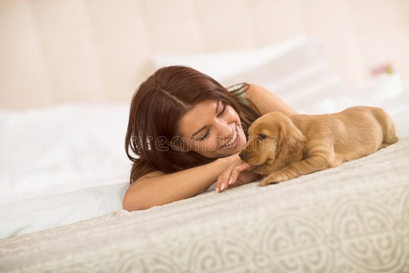 A menina e seu animal de estimação do cachorrinho apreciam na cama imagens de stock