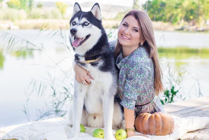 Menina e seu cão de puxar trenós do cão que andam perto do lago fotos de stock royalty free