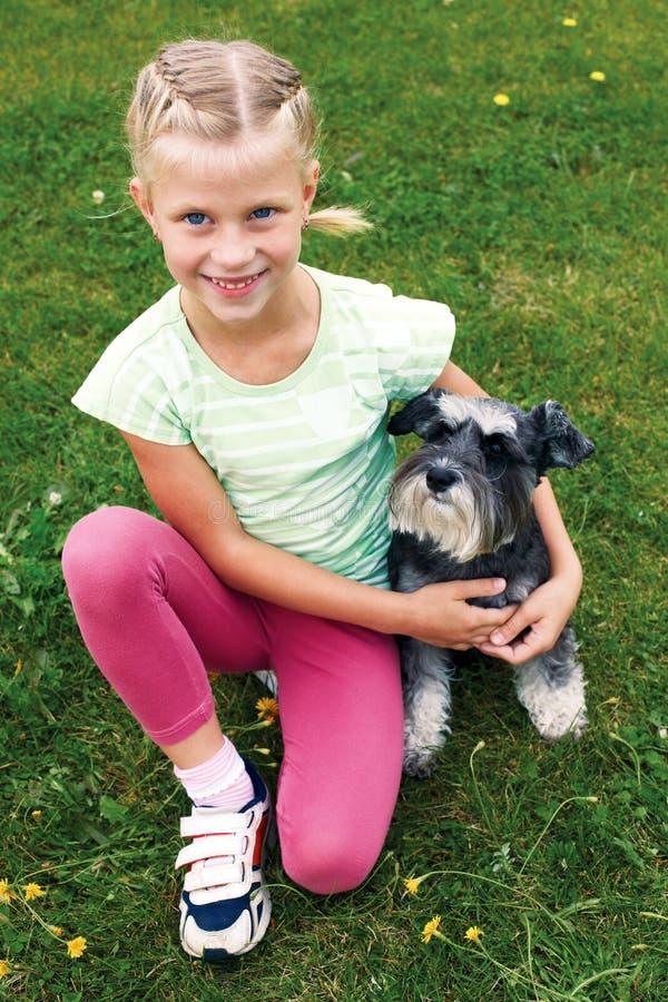 Menina e seu cão que encontram-se na grama no parque em um dia de verão fotos de stock royalty free