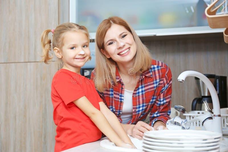 Menina e seus pratos de lavagem da mãe imagem de stock royalty free