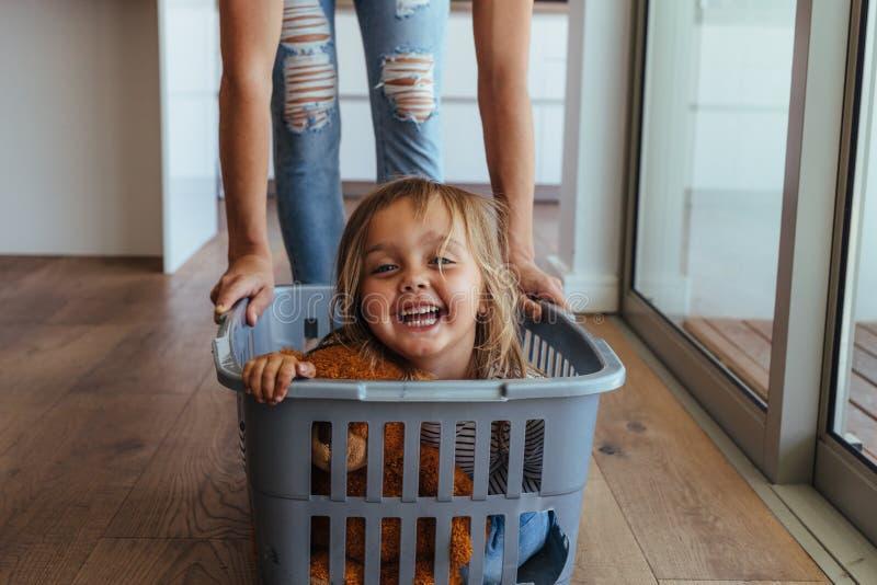 Menina e sua mãe que têm o divertimento que faz a lavanderia imagens de stock