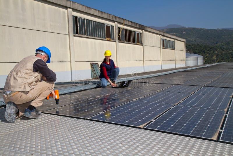 Menina e trabalhador qualificado novos do coordenador em um telhado foto de stock