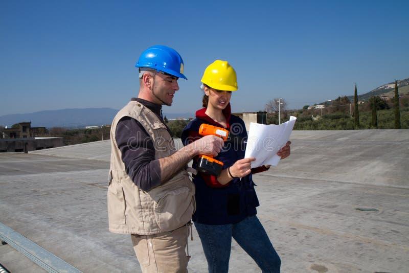 Menina e trabalhador qualificado novos do coordenador em um telhado fotos de stock