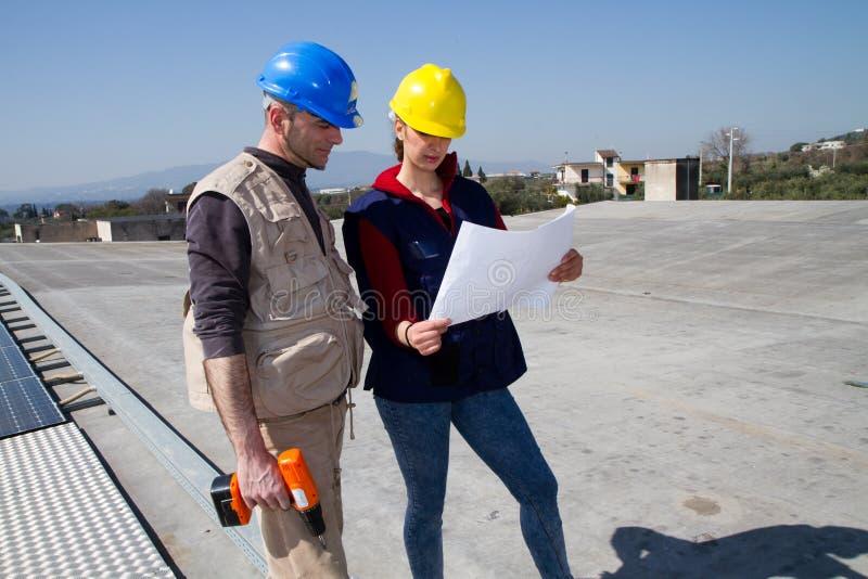 Menina e trabalhador qualificado novos do coordenador em um telhado imagem de stock