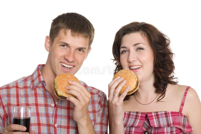 Menina e um indivíduo que come cheeseburgers imagens de stock royalty free