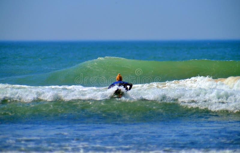 A menina editorial do surfista na vala Plains a praia Montauk New York fotografia de stock royalty free