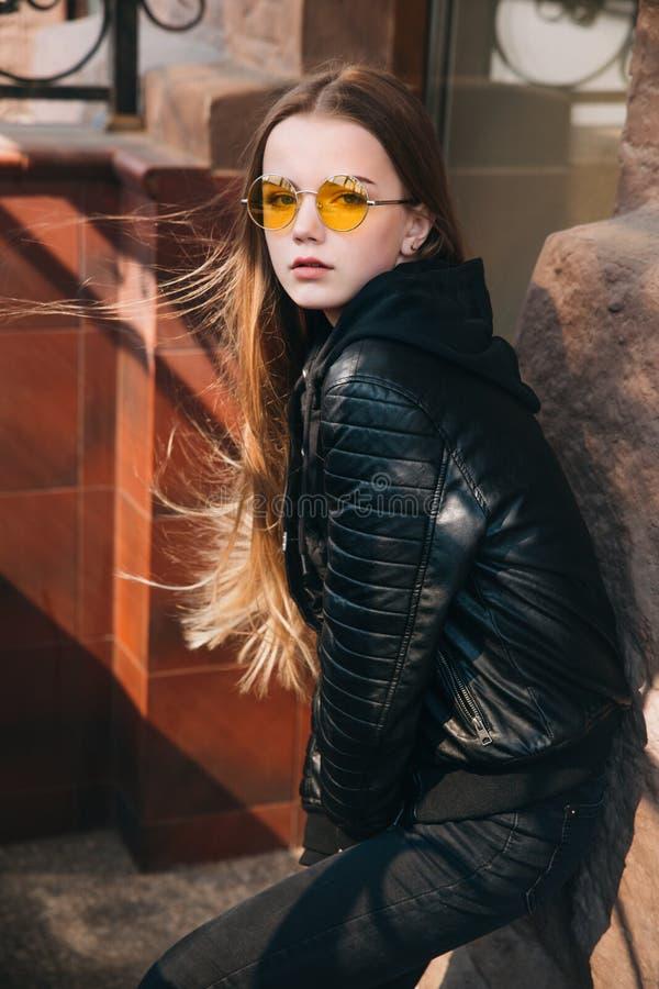 Menina elegante bonita com cabelo louro longo em óculos de sol amarelos na cidade, criança do adolescente da forma da rua, imagens de stock