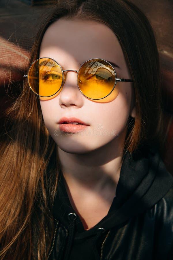 Menina elegante bonita com cabelo louro longo em óculos de sol amarelos na cidade, criança do adolescente da forma da rua, fotos de stock