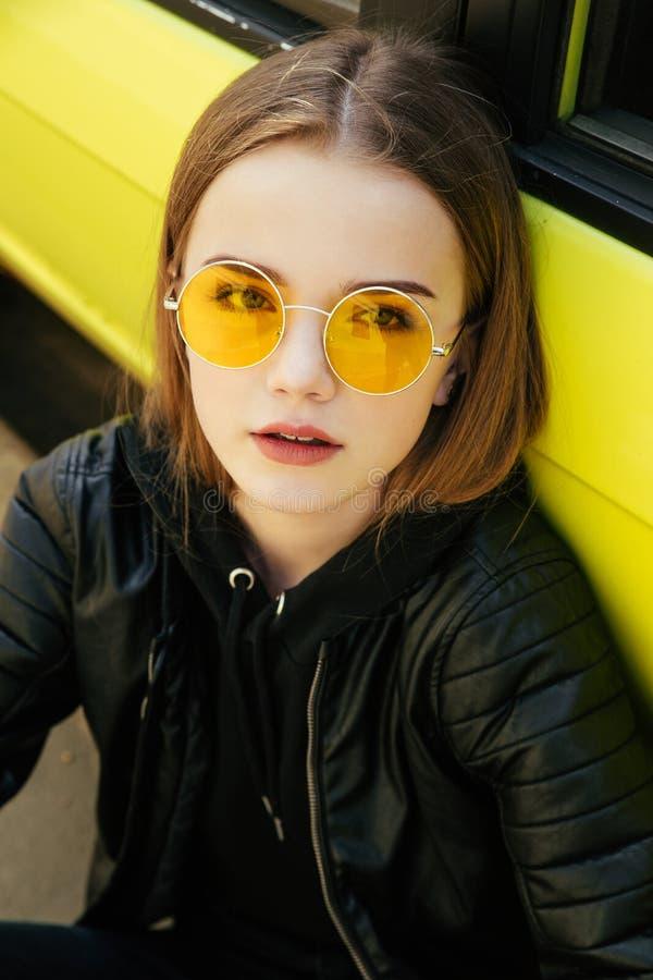 Menina elegante bonita do adolescente nos óculos de sol e no casaco de cabedal que levantam sobre o carro amarelo exterior foto de stock royalty free