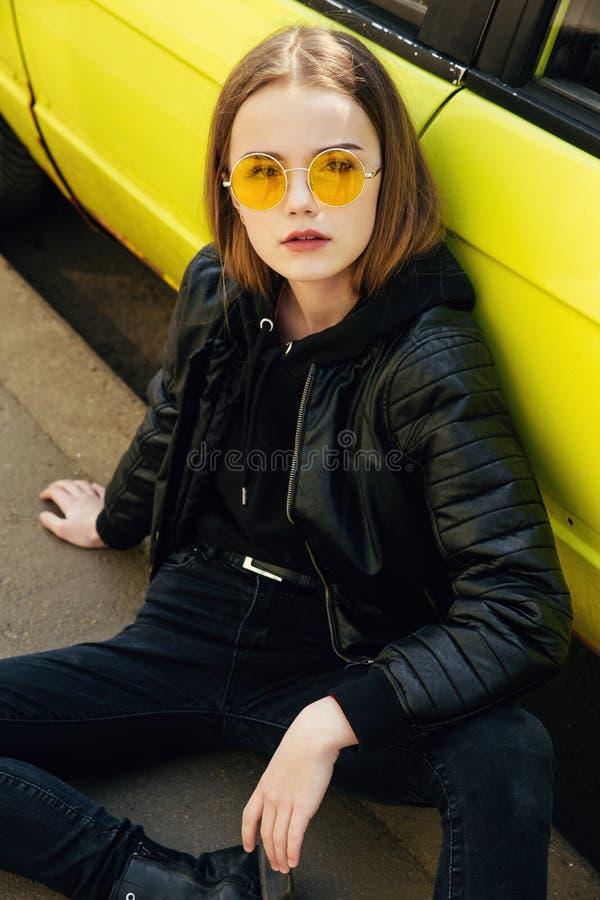 Menina elegante bonita do adolescente nos óculos de sol e no casaco de cabedal que levantam sobre o carro amarelo exterior imagens de stock