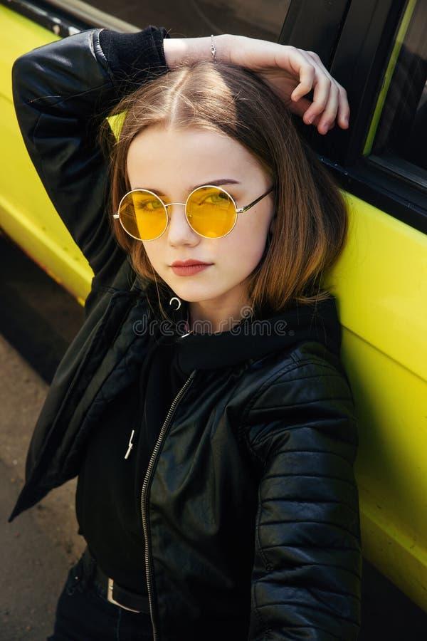 Menina elegante bonita do adolescente nos óculos de sol e no casaco de cabedal que levantam sobre o carro amarelo exterior imagem de stock royalty free