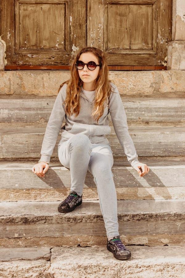 A menina elegante bonita nova nos óculos de sol está sentando-se nas etapas de pedra na porta de madeira velha em Antalya imagem de stock royalty free