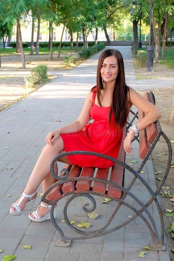 Menina elegante bonita que senta-se no corpo completo do banco de parque imagem de stock royalty free
