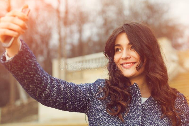 Menina elegante bonita que toma um selfie com smartphone fotos de stock royalty free