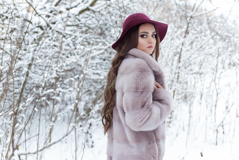 Menina elegante bonito bonita em um casaco de pele e em um chapéu que anda na manhã gelado brilhante da floresta do inverno fotografia de stock