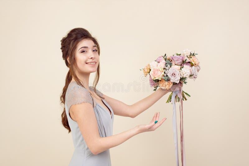 A menina elegante com um corte de cabelo em um vestido e em uma composi??o azuis macios est? guardando um ramalhete de um ramalhe fotografia de stock royalty free
