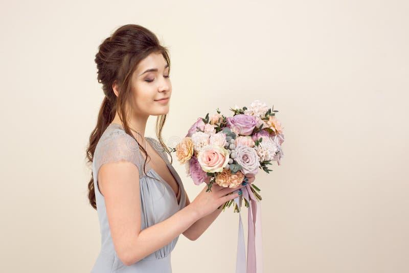 A menina elegante com um corte de cabelo em um vestido e em uma composi??o azuis macios est? guardando um ramalhete de um ramalhe imagens de stock royalty free