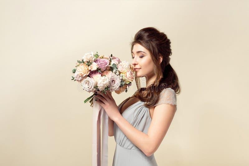 A menina elegante com um corte de cabelo em um vestido e em uma composi??o azuis macios est? guardando um ramalhete de um ramalhe fotos de stock
